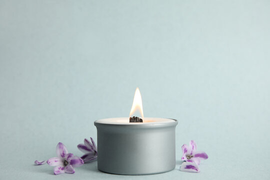 Beautiful candle with wooden wick and flowers on light background