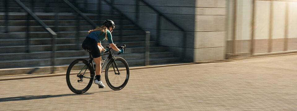 Professional female cyclist in cycling garment and protective gear riding bicycle in city, rushing and passing buildings while training outdoors on a daytime