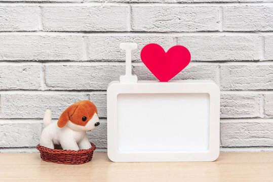 Toy puppy pet in a basket next to a frame with the inscription I and red heart and copy space for your text.