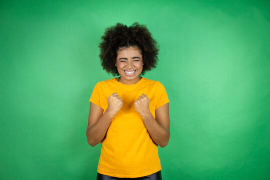 African american woman wearing orange casual shirt over green background very happy and excited making winner gesture with raised arms, smiling and screaming for success.