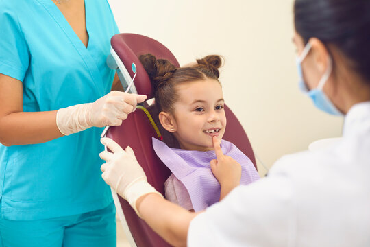 Little girl in a dental office shows two female dentists a tooth that worries her.