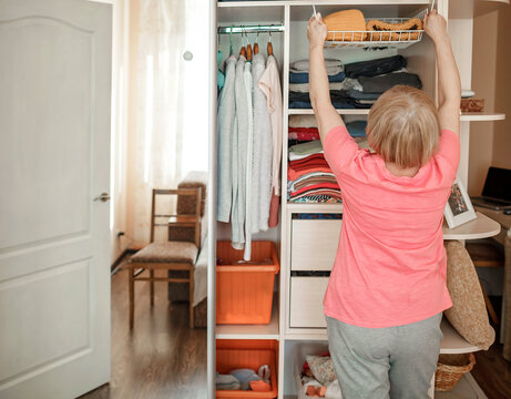 Senior woman choosing outfit from wardrobe closet with clothes and home stuff. Cleaning, organizing and order in the closet