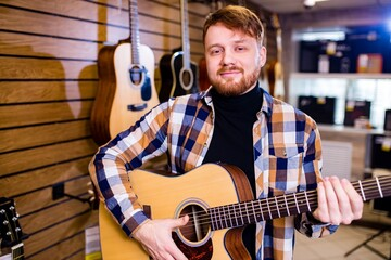 redhaired bearded handsome man in brown plaid casual shirt choosing a guitar in a music store