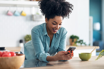 Beautiful afro woman sending messages with her smartphone while eating noodles with chopsticks in...