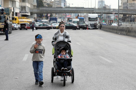 A woman pushes a baby cart along a blocked highway during a protest against the fall in Lebanese pound currency and mounting economic hardships, in Jal el-Dib
