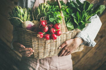 Fototapeta Woman farmer in linen apron holding basket of fresh organic garden vegetables and greens in hands, rustic wooden wall at background