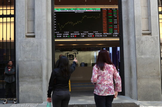 Women observe an electronic board showing the recent fluctuations of market indices outside of the Brazil's B3 Stock Exchange in downtown Sao Paulo