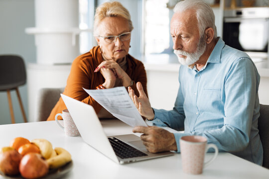 Frustrated senior couple sitting at home and checking their home finances