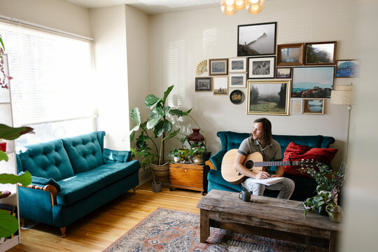 Young man sitting on couch at home with guitar