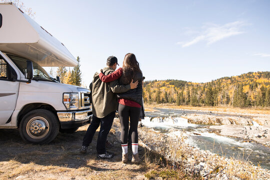 Couple hugging next to RV on river bank in forest