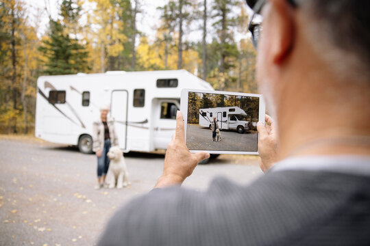 Man using digital tablet to take photo of wife and dog in front of RV