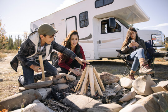 Mother and son building campfire next to RV