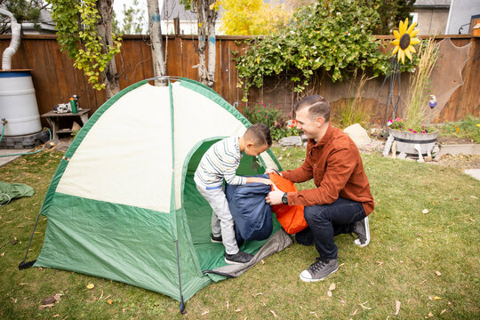 Father helping son with camping in backyard