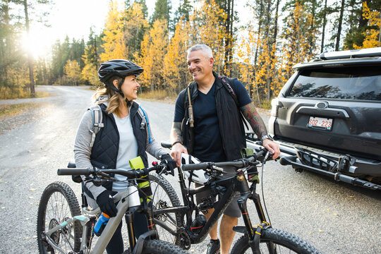 Couple with SUV preparing to go for a bike ride in forest