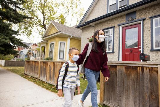 Siblings wearing facemask walking along pavement