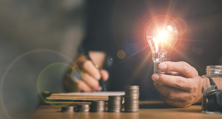 Fototapeta businessman holding lightbulb with using calculator to calculate and money stack. idea saving energy and accounting finance in home office concept, Business, finance, investment, Financial planning.