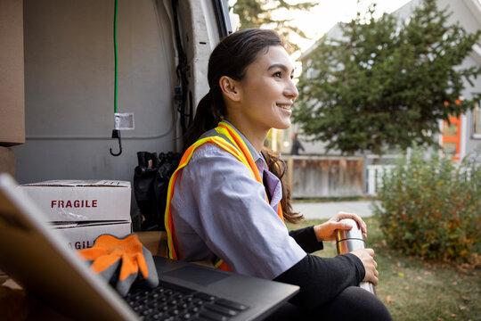 Portrait of courier worker taking break at rear of van