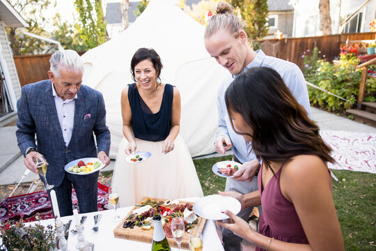 Mature newlyweds and guests enjoying appetizer at wedding reception