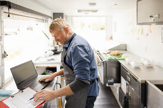 Food truck owner working with laptop