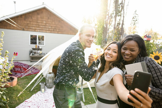 Young newlyweds celebrating with champagne, taking selfie with friend