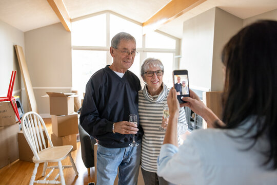 Daughter photographing senior parents celebrating new home
