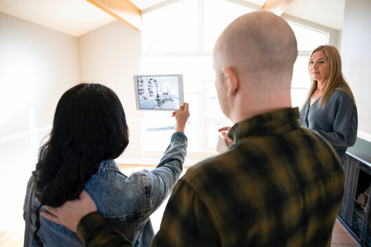Realtor helping couple with digital tablet in empty living room