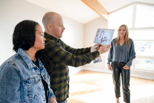 Realtor watching couple with digital tablet at open house
