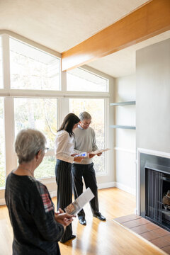 Realtor helping senior couple with brochures in open house living room