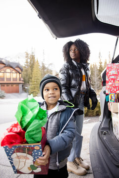 Family unloading Christmas presents from car