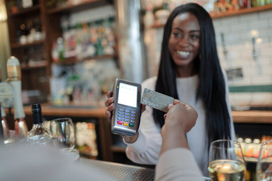 Customer paying female bartender with smart card in bar