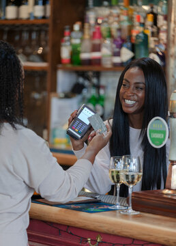 Customer paying female bartender with smart card at pub counter