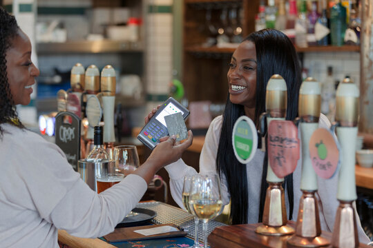 Customer paying happy female bartender with smart card in pub