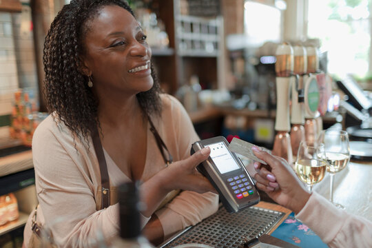 Customer paying female bartender with smart card at bar