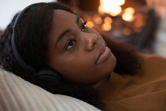 Close up serene woman listening to music by fireplace