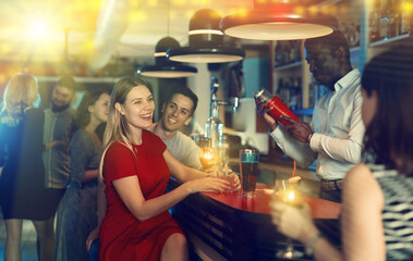 Cheerful girl with best friends partying in bar, dancing and toasting drinks. High quality photo