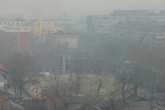 Student stands on a sports field shrouded in smog on a polluted day in Beijing