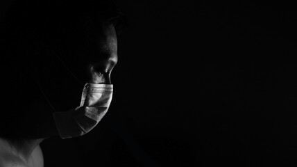 Covid-19 pandemic awareness. In the dark low key monochrome male profile wearing protection face...