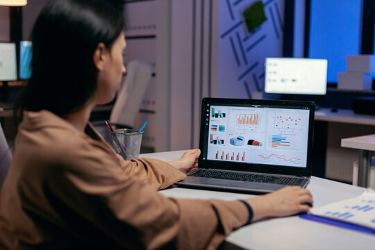 Busy business woman working on financial reports checking statistics graphs, looking at laptop in the course of deadline. Businesswoman looking at statistics on laptpop screen sitting at her workplace
