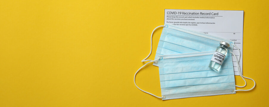 Vaccination record card, vaccine and masks on yellow background