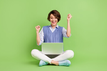 Portrait of attractive trendy lucky cheerful girl sitting lotus position using laptop rejoicing having fun isolated over green color background