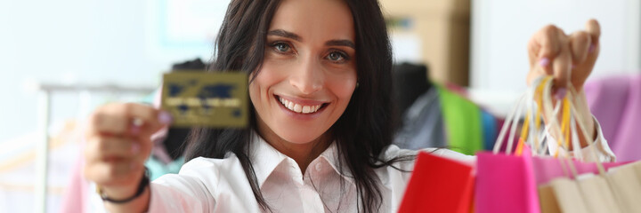 Obraz Happy girl at home shows credit card and packages. Make purchases with credit card during self-isolation. Modern virtual shopping. Help from an independent stylist. Images are composed - fototapety do salonu