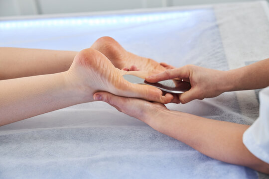 Massage professional treating patient foot with gua sha scraper
