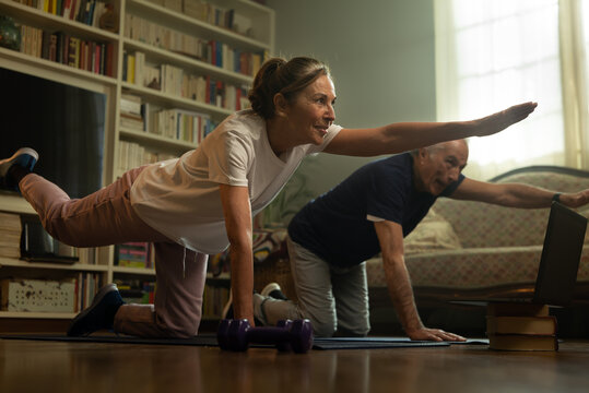 Cinematic shot of happy mature senior couple exercising together with online tutorial at home. Concept of healthy lifestyle, fitness online, recreation, well being, elderly, e-courses, technology.