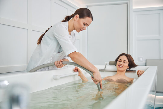 Woman beauty salon worker dipping hose into hot tub
