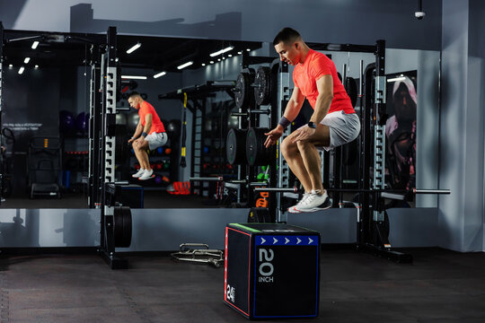 A focused athlete in an orange T-shirt and gray shorts jumps on the gym box in a darkened fitness studio with a mirror. Sports lifestyle, healthy life