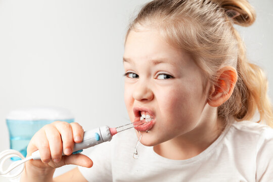 Water flosser. Girl child cleans his teeth, care for the oral cavity in childhood.