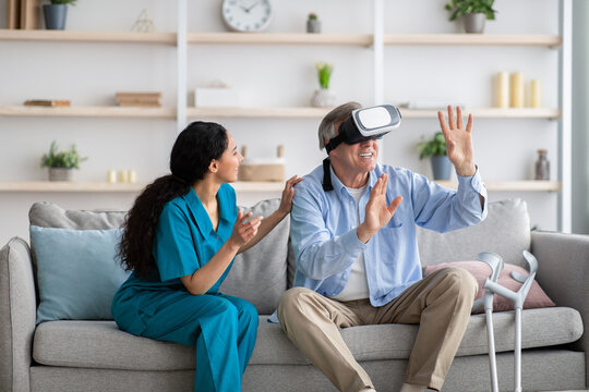 Disabled senior man using VR headset with young nurse, exploring augmented reality at home