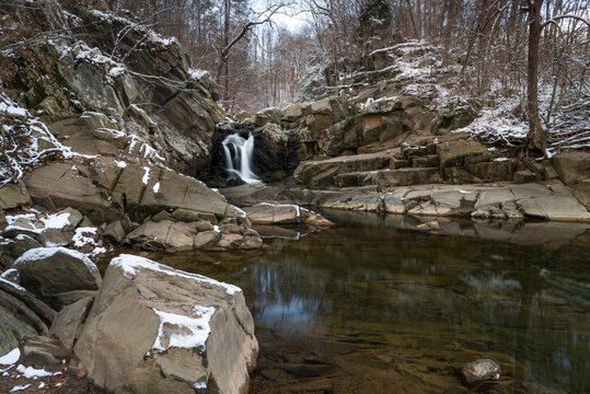 The waterfall at Scott's Run Nature Preserve in Northern Virginia under a cloudy afternoon winter sky with a light dusting of snow on the rocks.