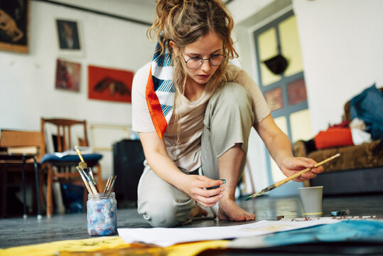 Horizontal image of a pretty female artist sitting on the floor in the art studio and painting on paper with a brush. A woman painter with glasses painting with watercolors in the workshop.