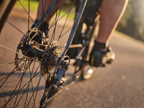 Close up shot of bicycle speed rear cassette with chain and brake disk. Cyclist riding road bike at sunset